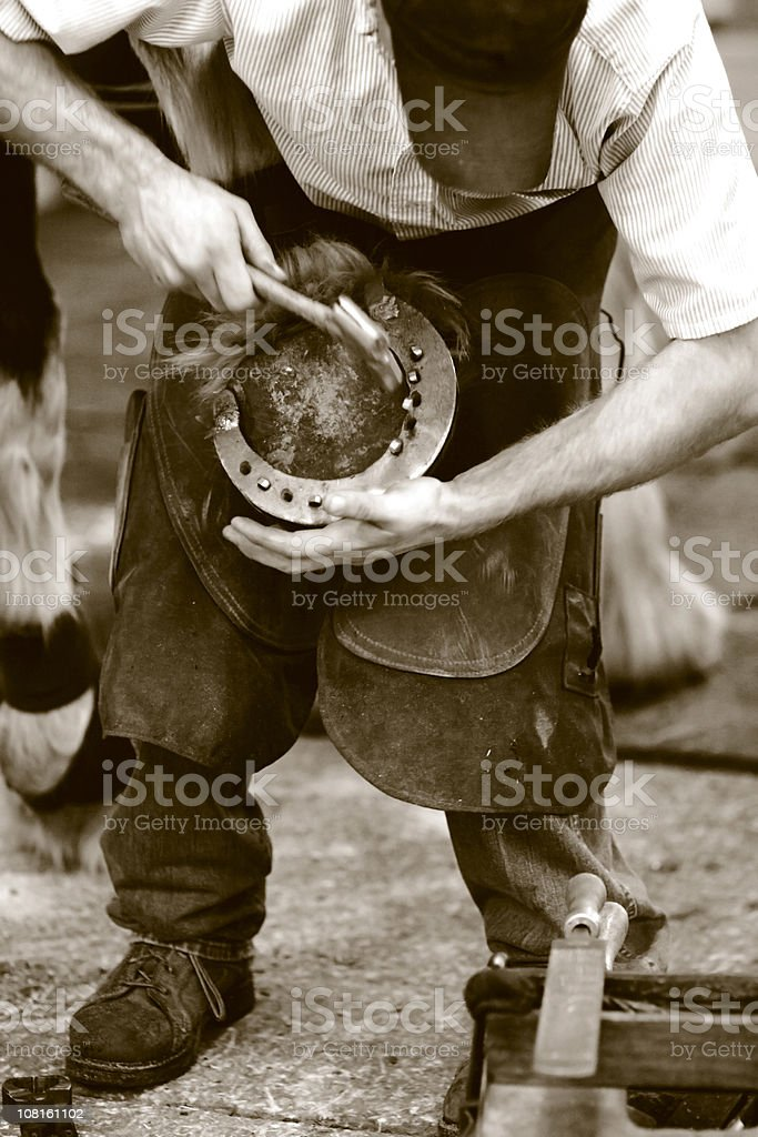 Farrier Replacing Horse Shoe, Sepia Toned stock photo