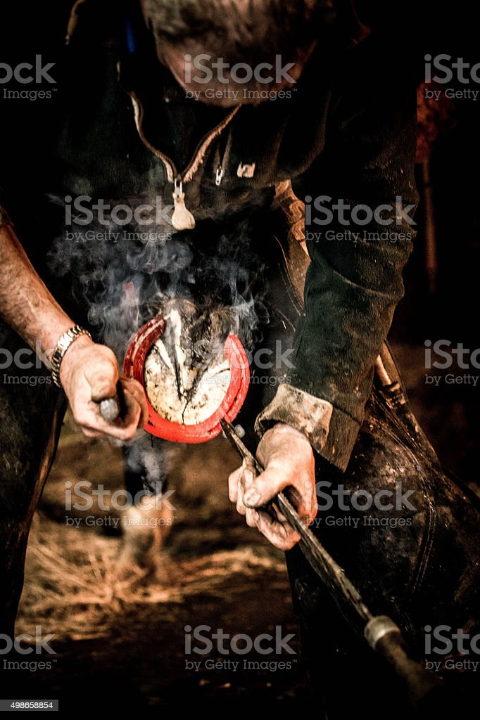 farrier with hot horse shoe stock photo