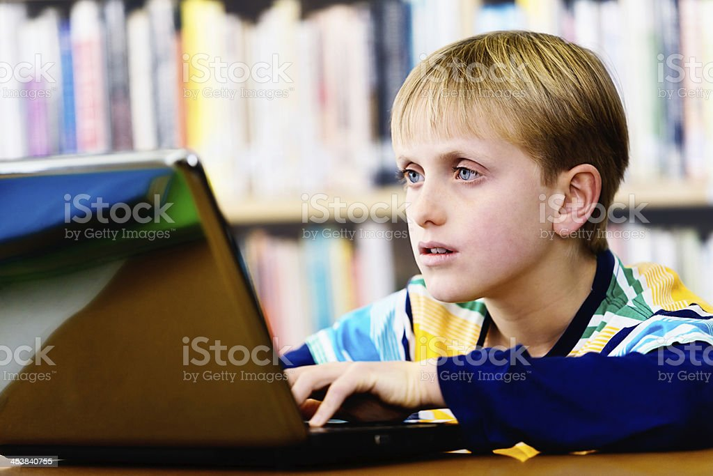 Fascinated little boy in library using computer: learning is fun! stock photo