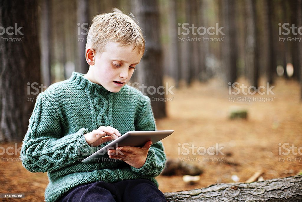 Fascinated little boy studies new tablet-style pc in forest stock photo