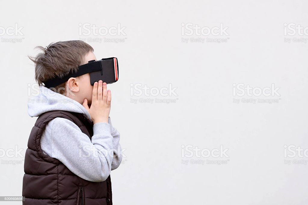 Fascinated little boy using VR virtual reality goggles stock photo