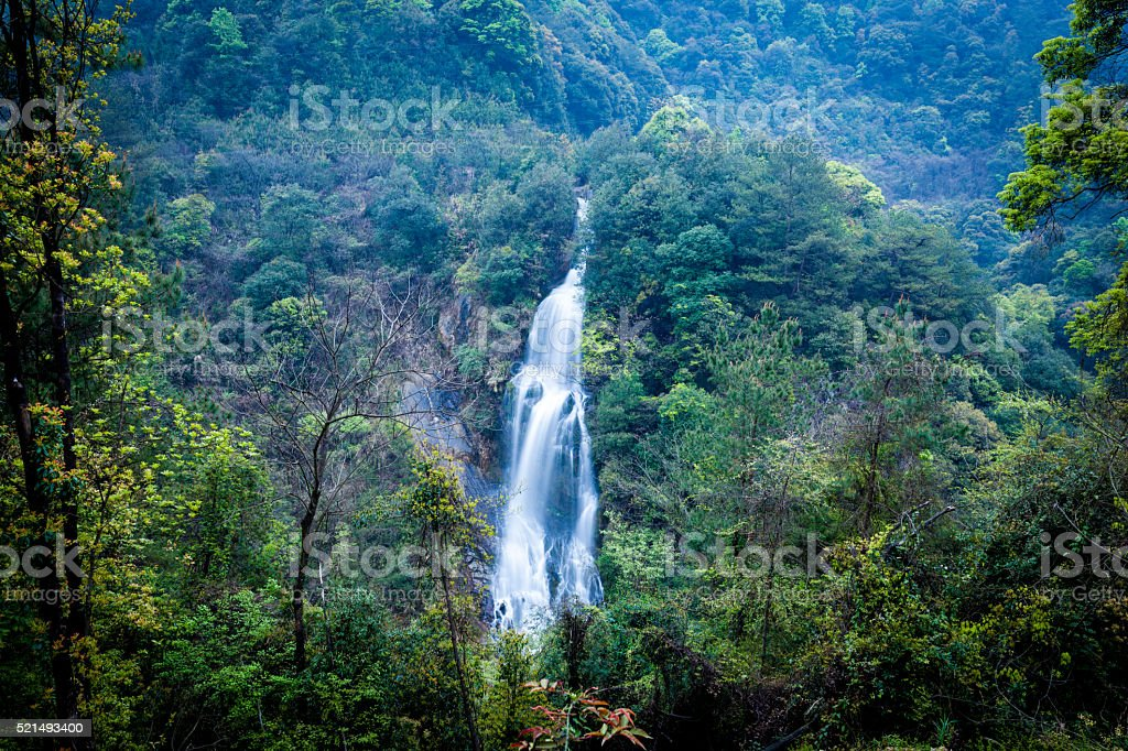 fascinating waterfall in forest at sunny day stock photo