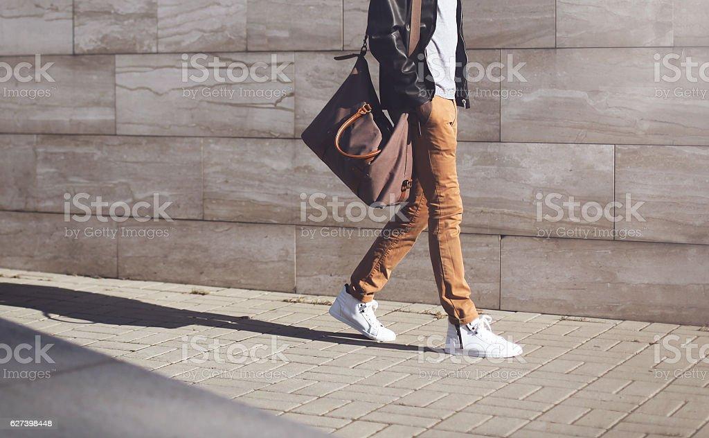 Fashion african man in black jacket walking in city stock photo