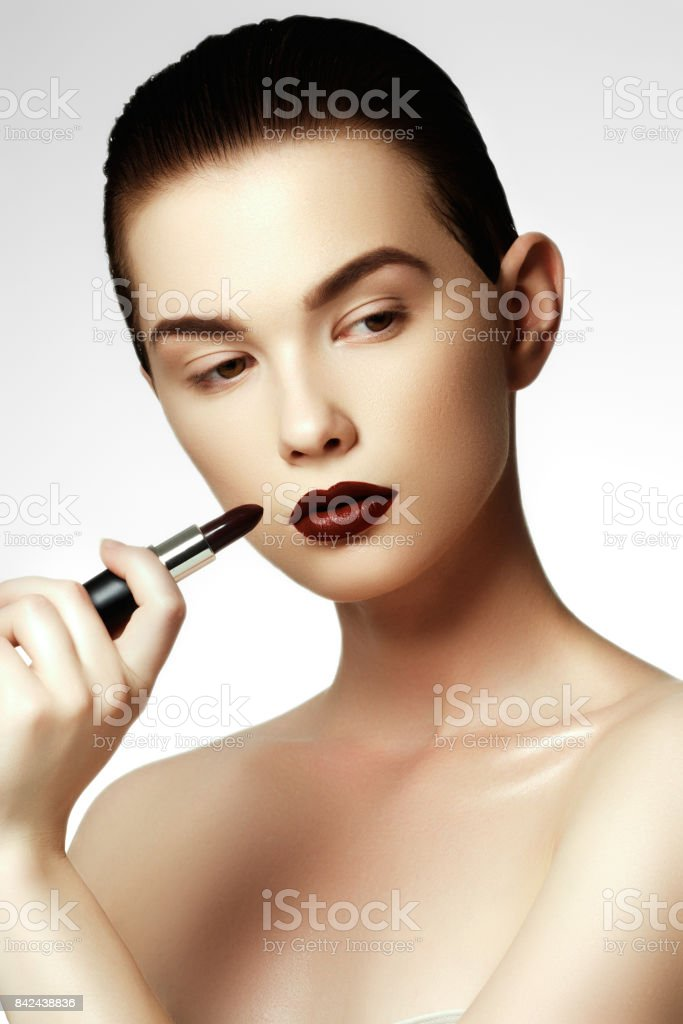 Fashion and beauty. Beautiful young woman with wine lipstick. Brunette model with dark red colored pomade. Beautiful model girl applying lipstick stock photo