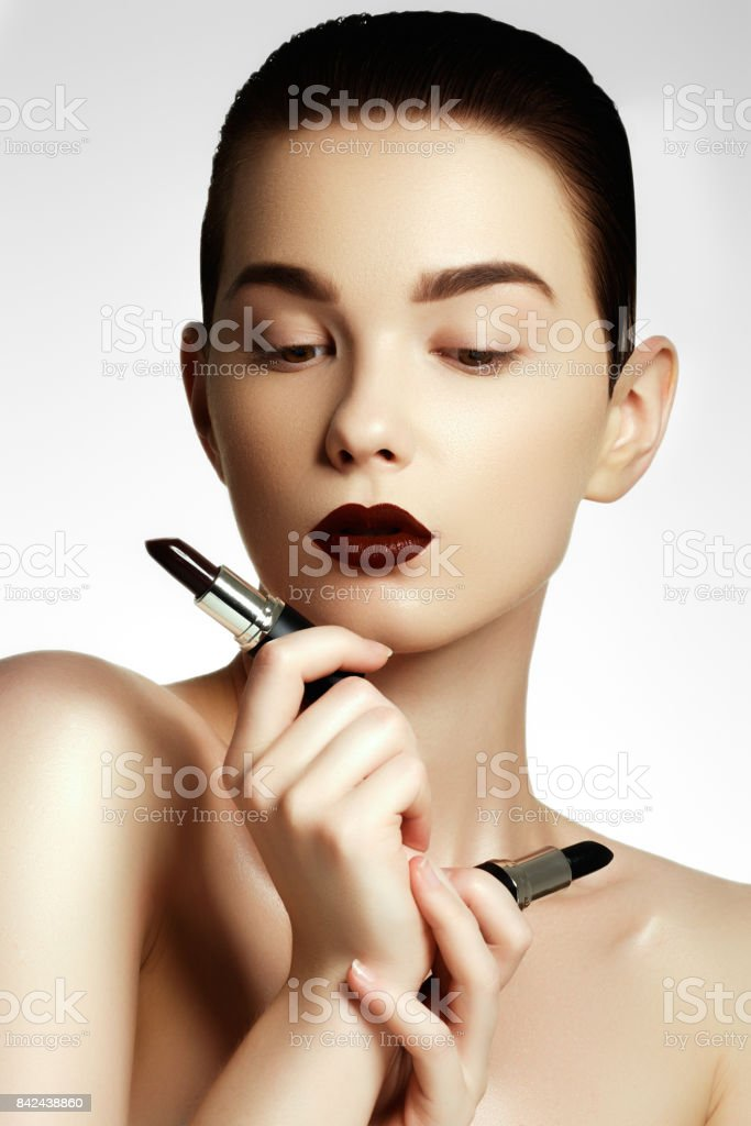 Fashion and beauty. Beautiful young woman with wine lipstick. Bunette model with dark red colored pomade. Beauty model applying lipstick stock photo