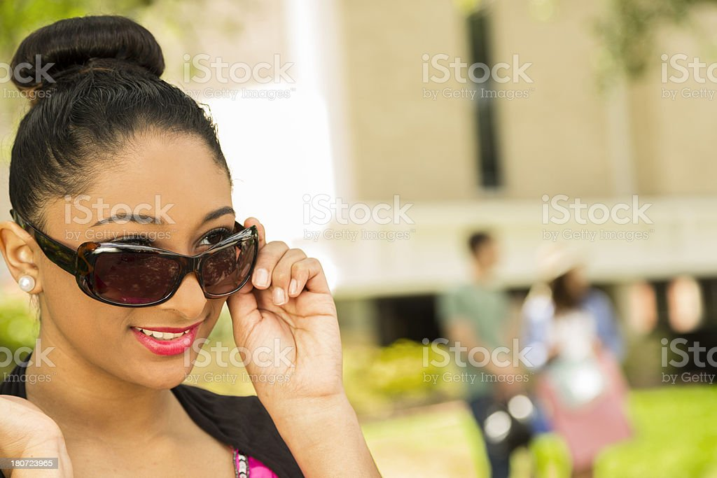 Fashion: Beautiful Young adult outdoors with friends in background. royalty-free stock photo