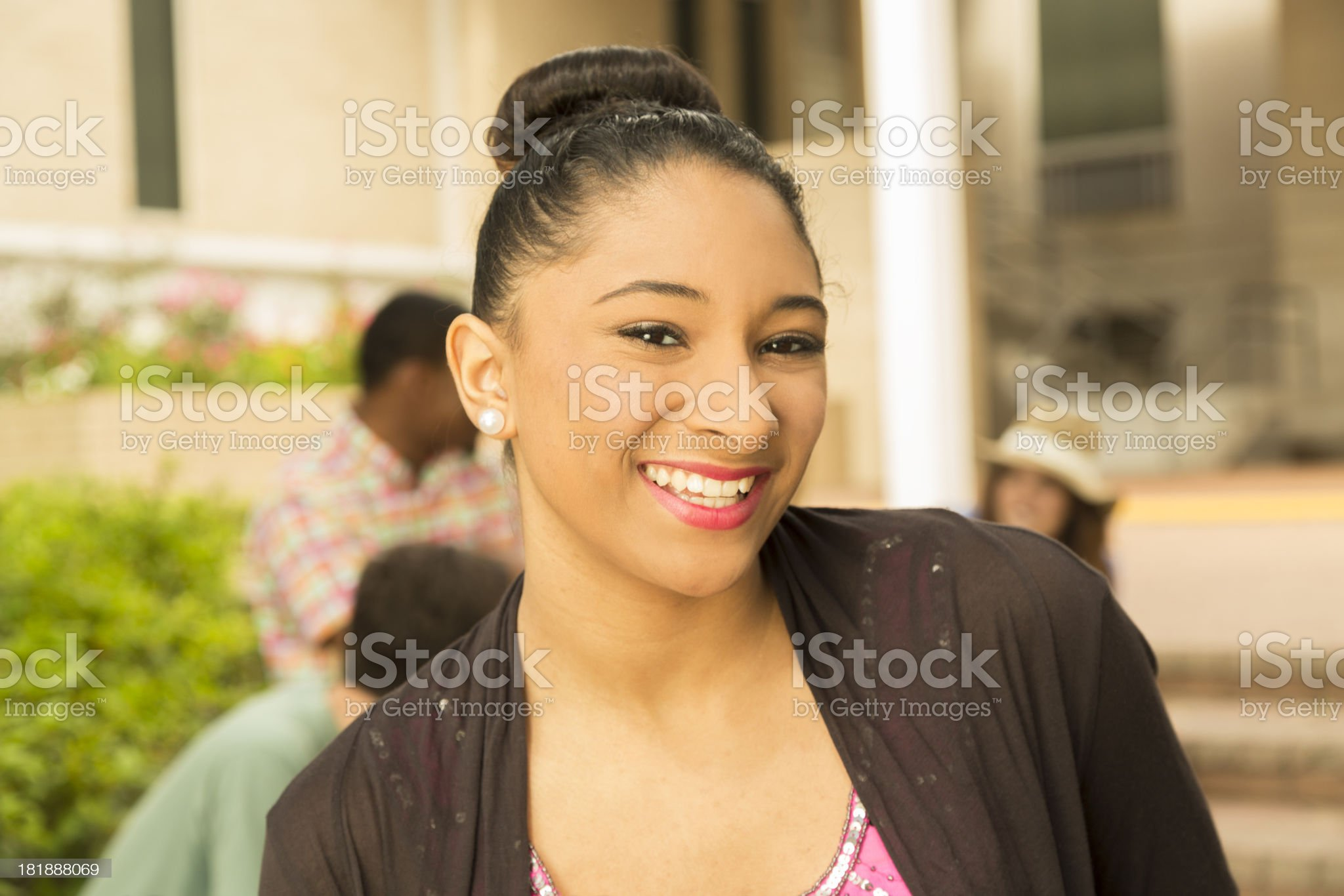 Fashion: Beautiful Young adult outdoors with friends in background royalty-free stock photo