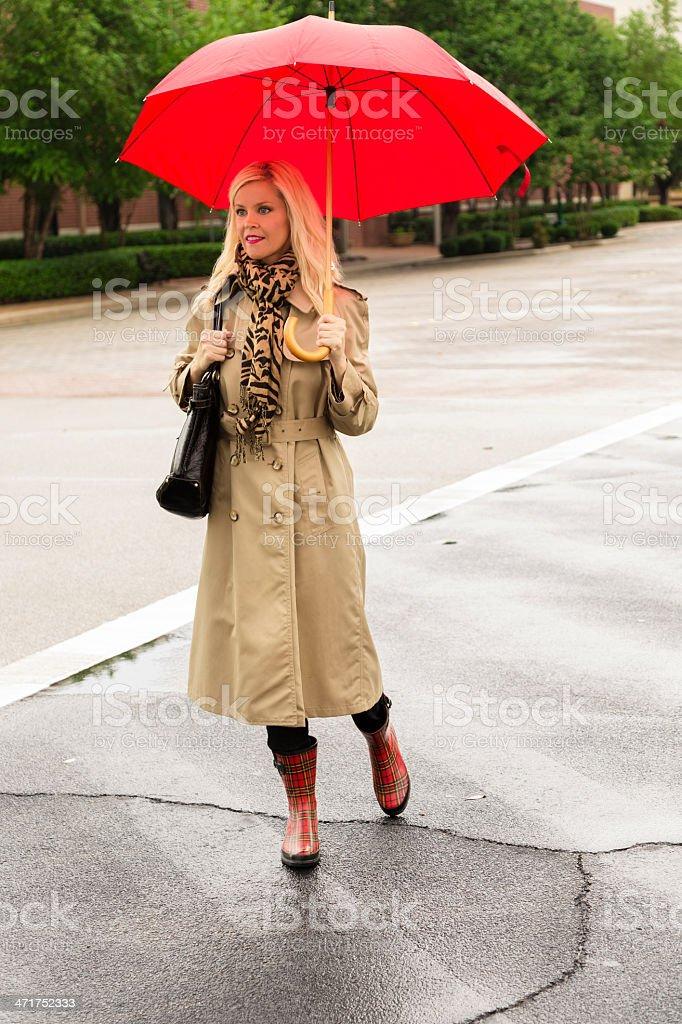Fashion: Businesswoman crossing street in rain. Holding umbrella, shopping. royalty-free stock photo