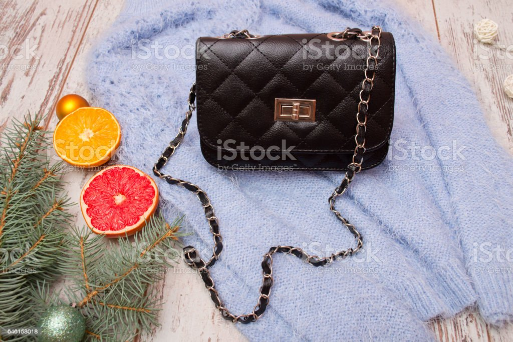 Fashion concept. Black female bag on sweater, spruce branch and orange stock photo