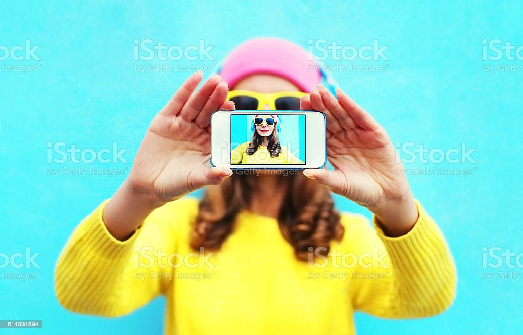 Fashion cool girl taking picture self portrait on smartphone colorful stock photo