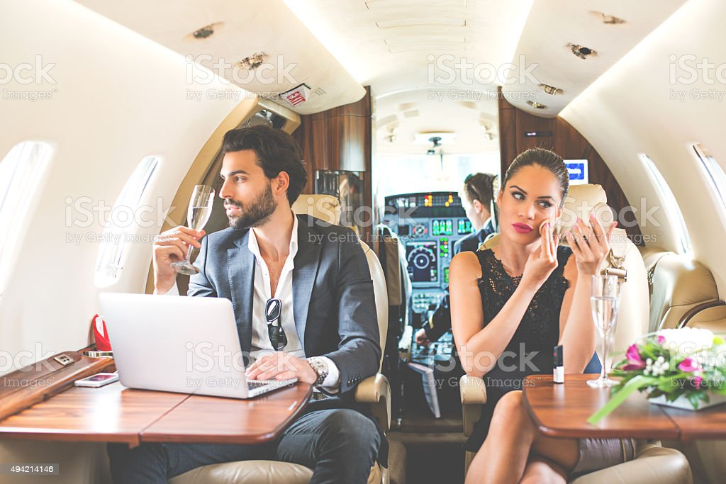Fashion couple inside private airplane stock photo