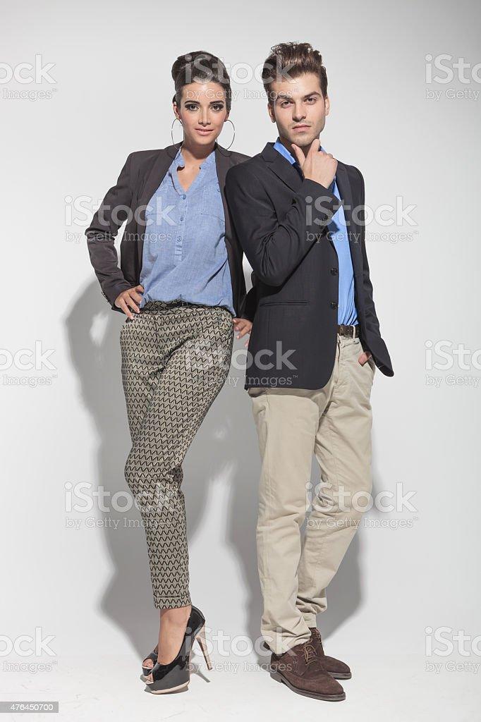 fashion couple posing on light grey background stock photo