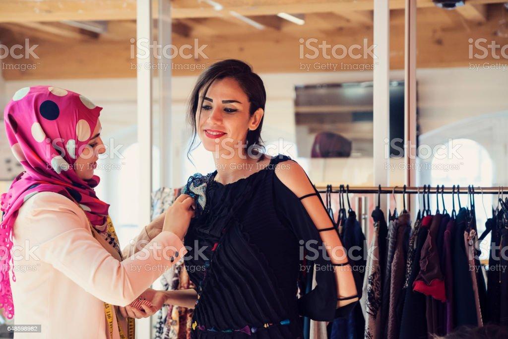 Fashion designer adjusting clothing on female model. stock photo