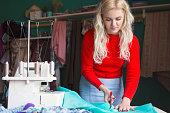 Fashion designer cutting clothing