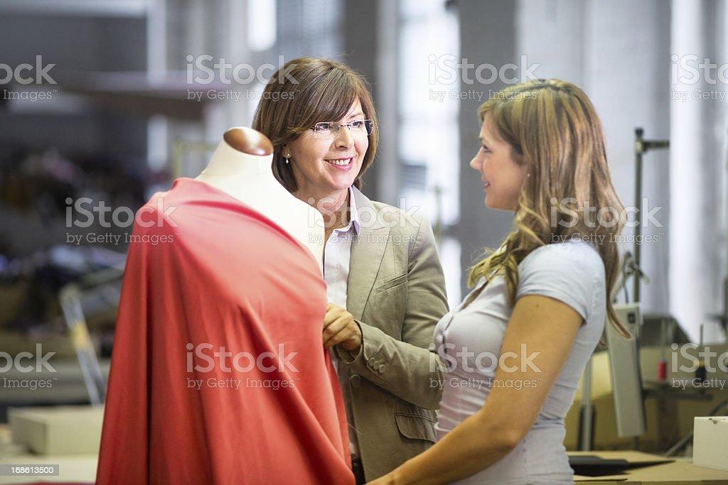 Fashion designer explaining her technique to customer royalty-free stock photo