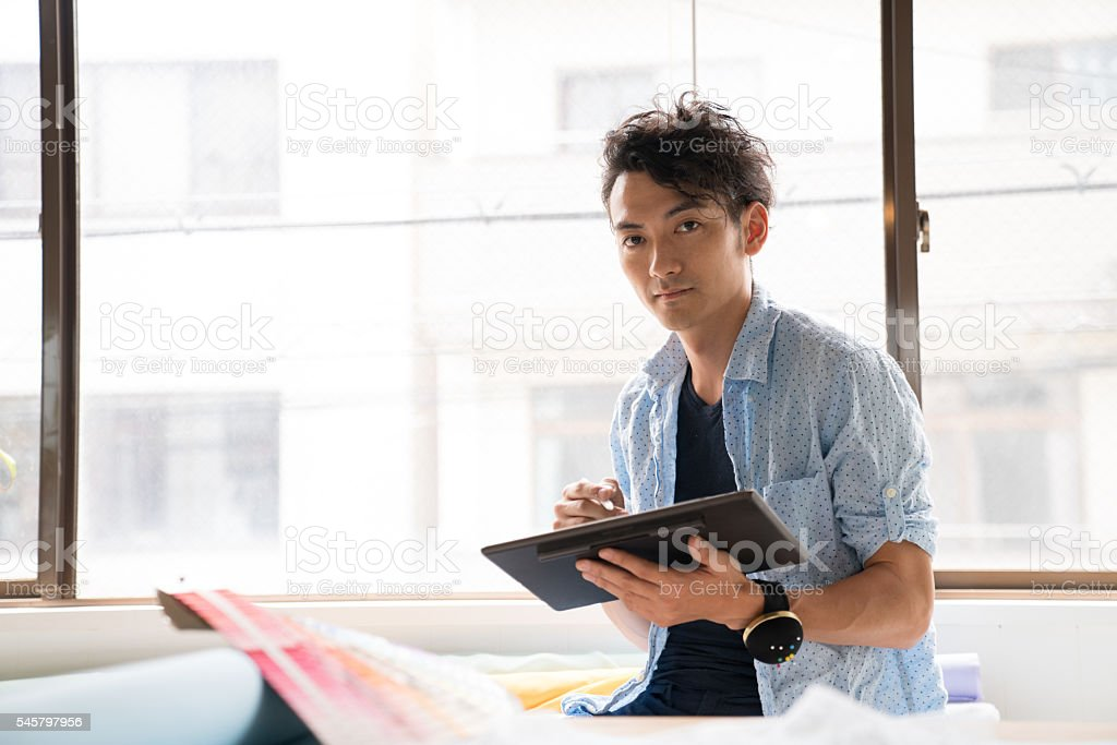 Fashion designer in his studio working with a digital tablet stock photo