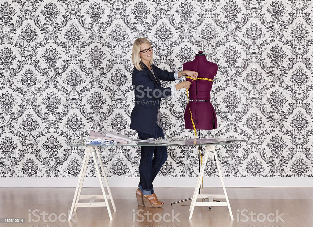 Fashion designer measuring a dress royalty-free stock photo