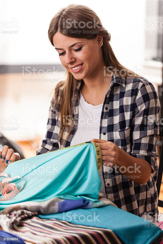 Fashion designer measuring and cutting cloth stock photo