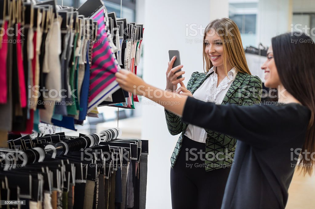 Fashion designer photographing swatches with camera phone stock photo