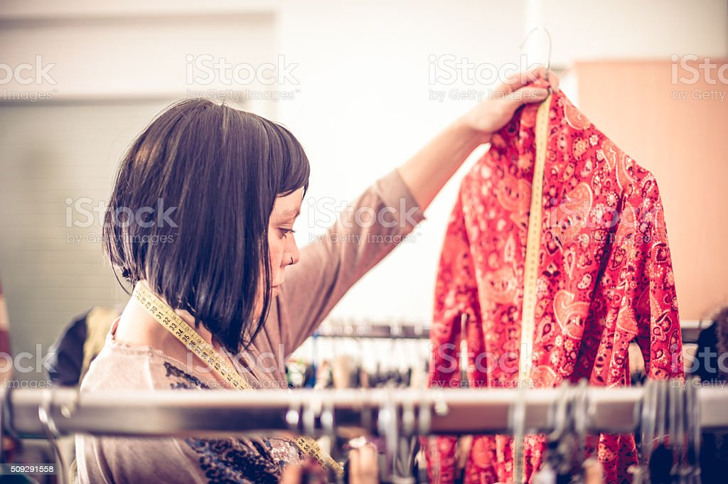 Fashion Designer Selecting Clothes from Clothes Rack stock photo