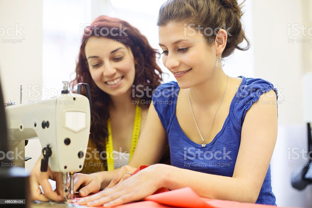 Fashion designer sewing fabrics with assistant stock photo