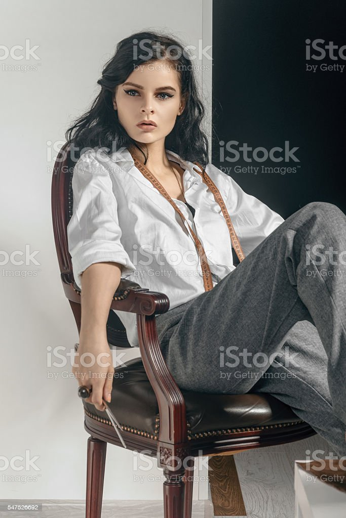 Fashion designer sitting with scissors in her hand. stock photo