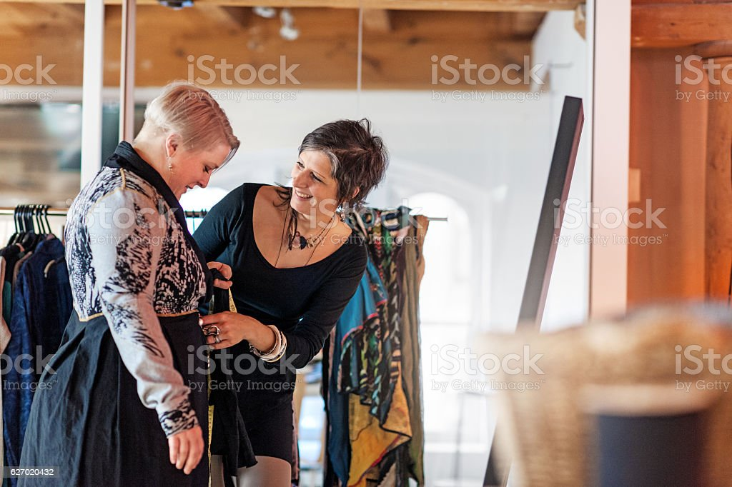 Fashion designer  taking customer measurement in clothing boutique stock photo