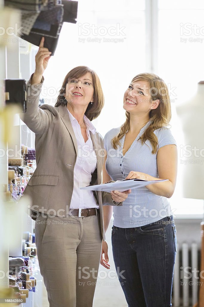 Fashion designer teaches young woman about fabrics royalty-free stock photo