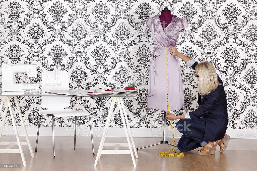 Fashion designer working with a measure tape royalty-free stock photo