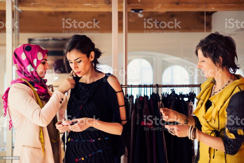 Fashion designers adjusting clothing on female model. stock photo