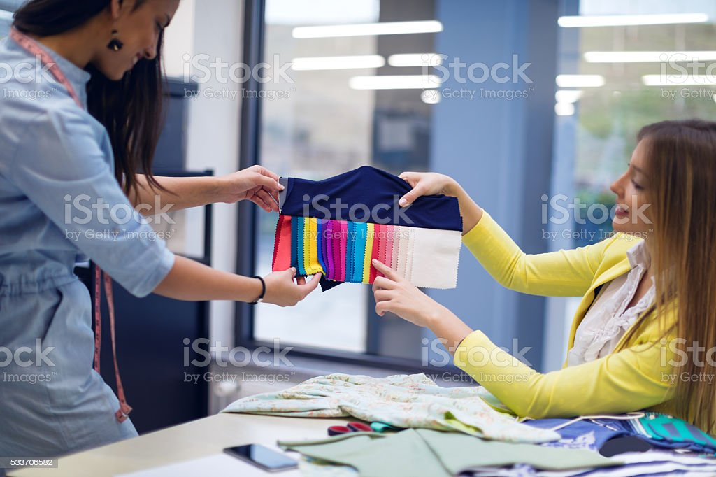 Fashion designers choosing from fabric samples stock photo