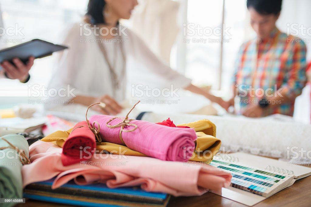 Fashion designers looking at fabric samples stock photo