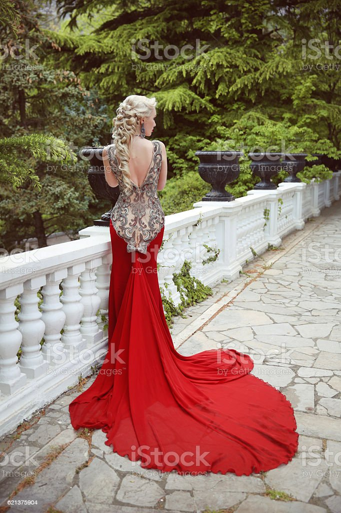 Fashion elegant blond woman model in red gown with train stock photo