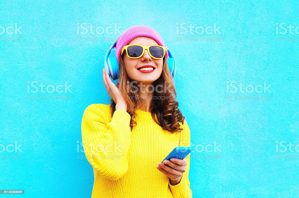 Fashion girl listening to music in headphones with smartphone colorful stock photo