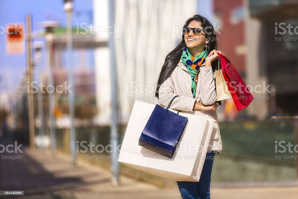 Fashion happy young woman standing with shopping bags in street stock photo