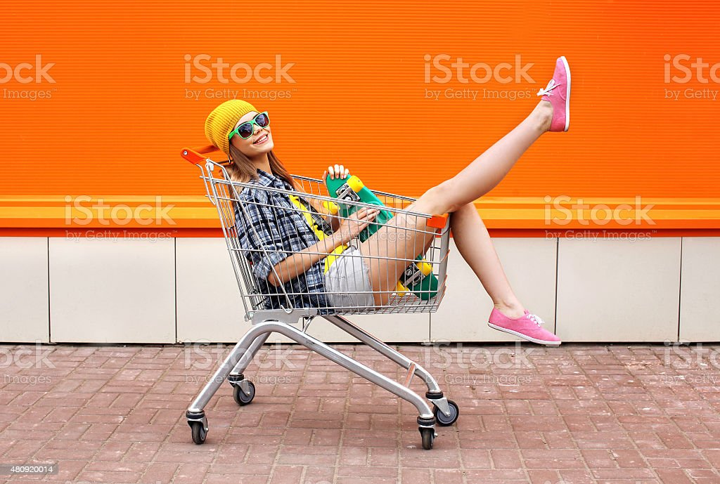 Fashion hipster cool girl with skateboard in shopping cart havin stock photo
