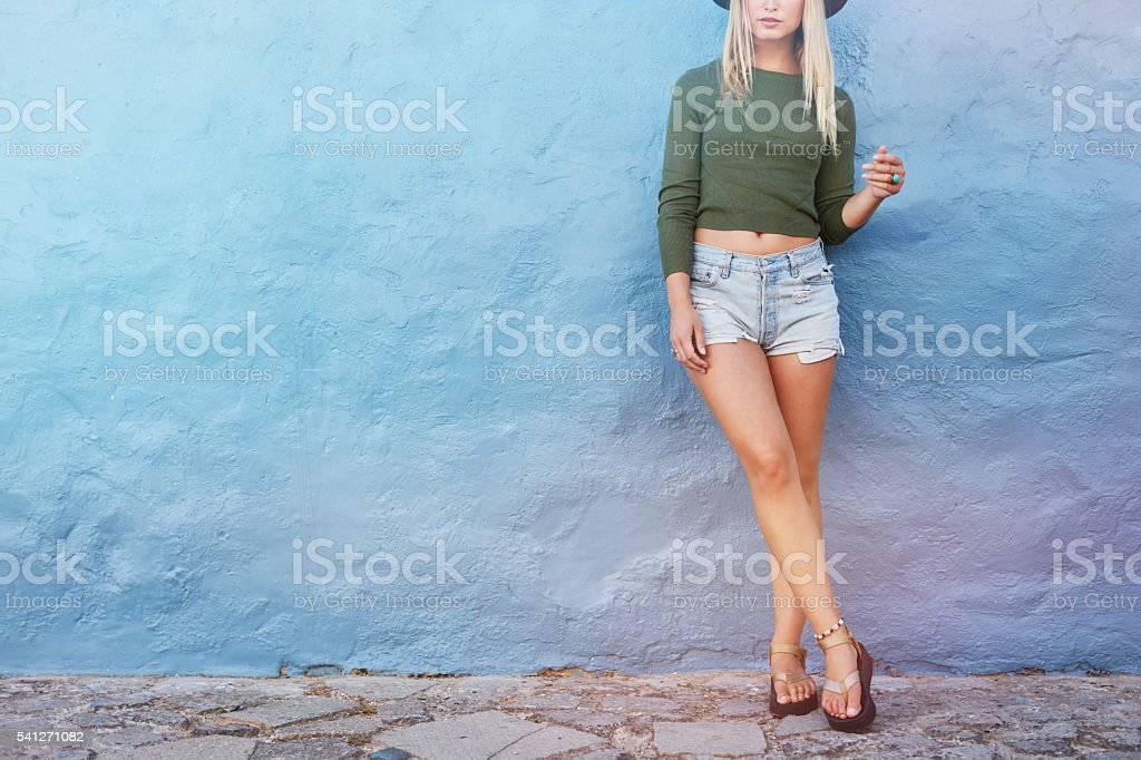 Fashion hipster woman posing near blue wall stock photo
