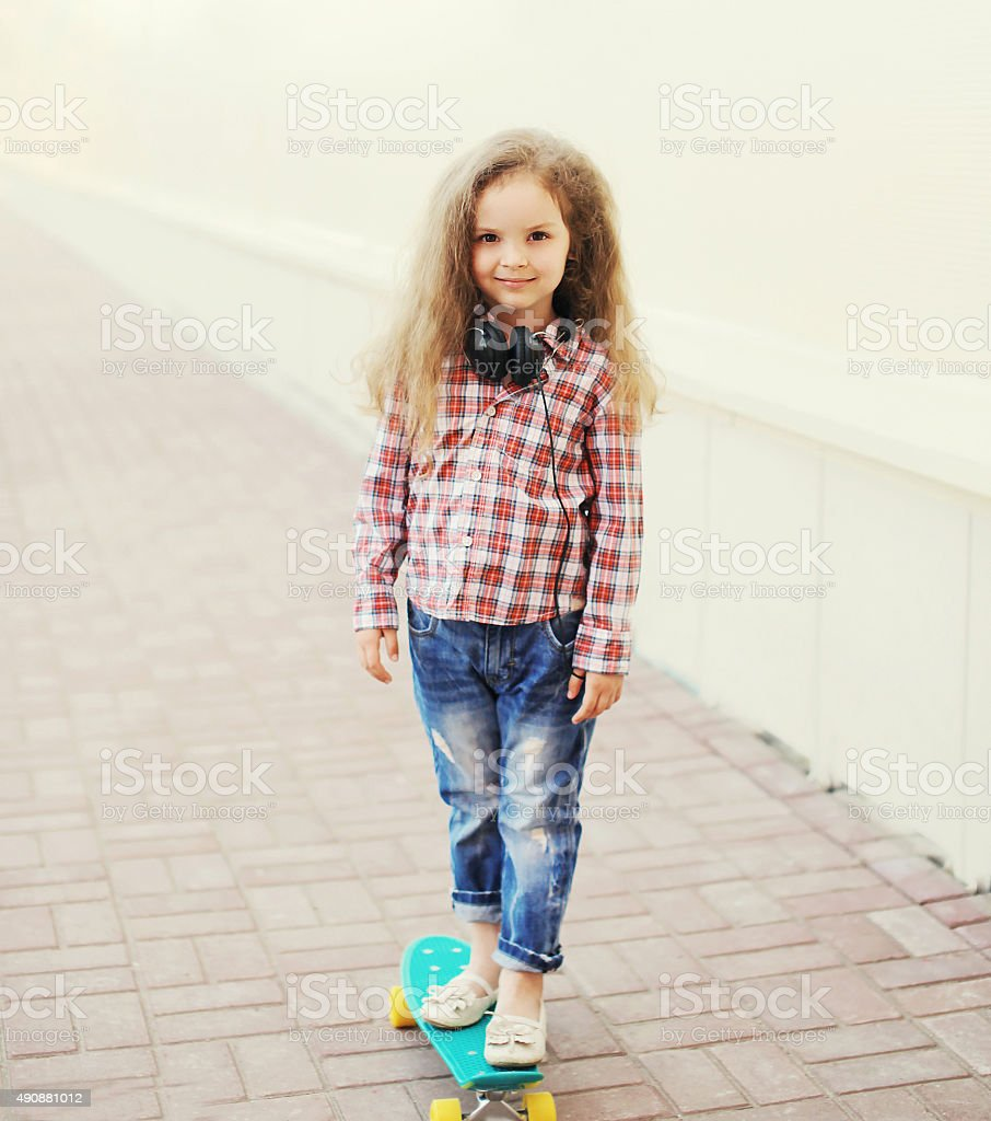 Fashion little girl child on skateboard in the city stock photo