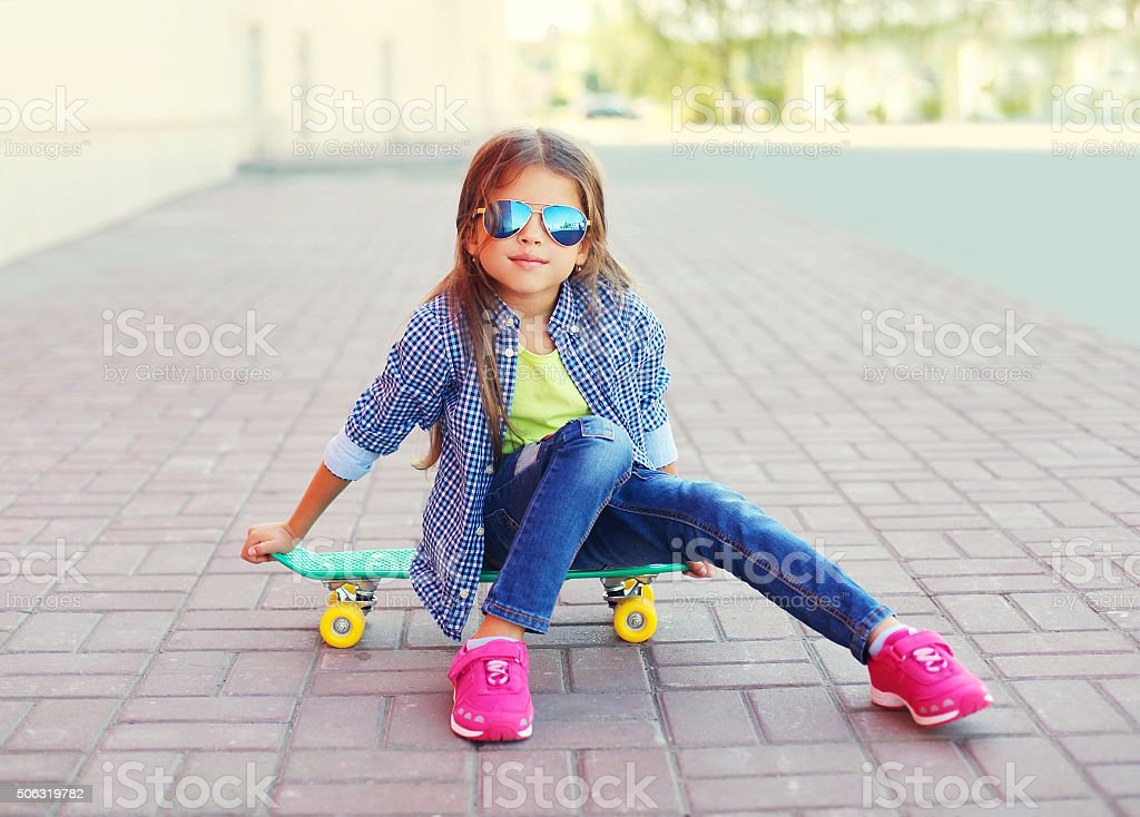 Fashion little girl child sitting on skateboard in city stock photo