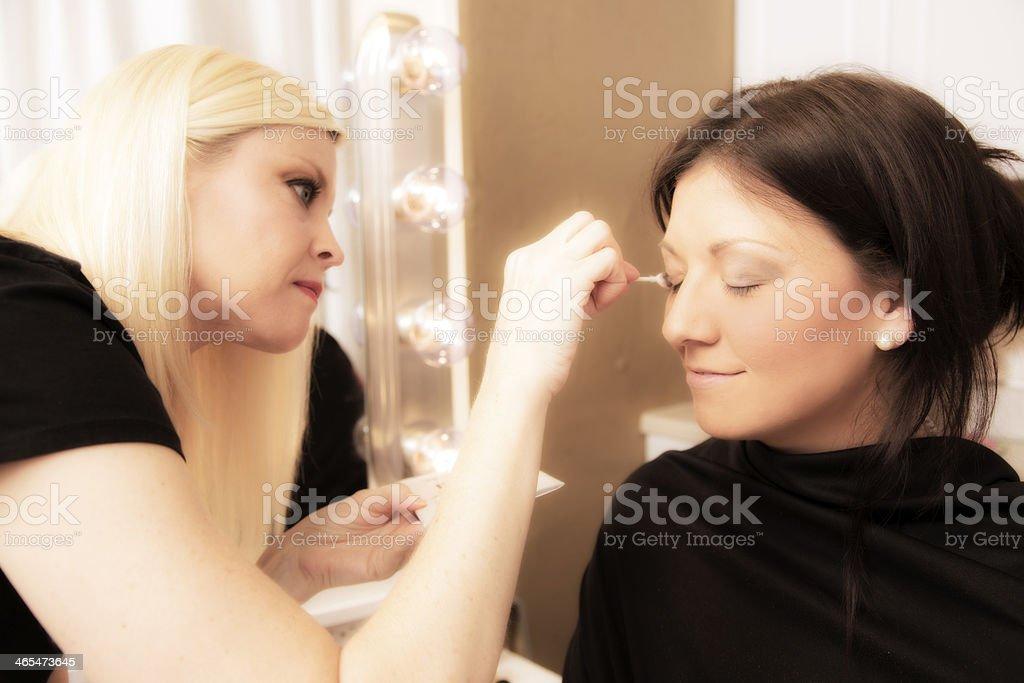 Fashion: Make up artist applies cosmetics to model. stock photo
