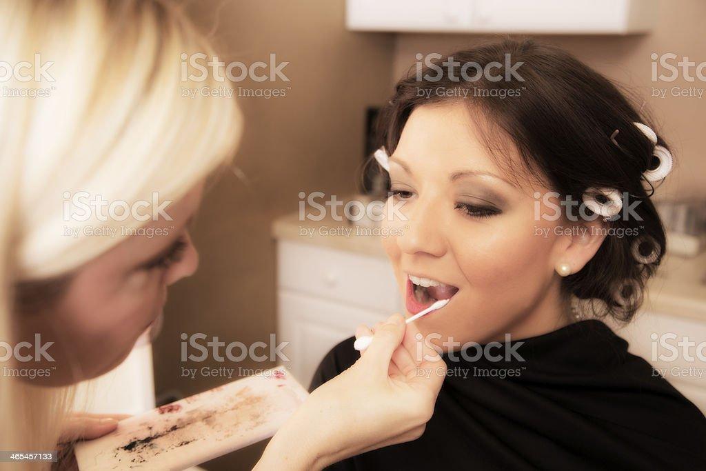 Fashion: Make up artist applies lipstick, cosmetics to model. stock photo