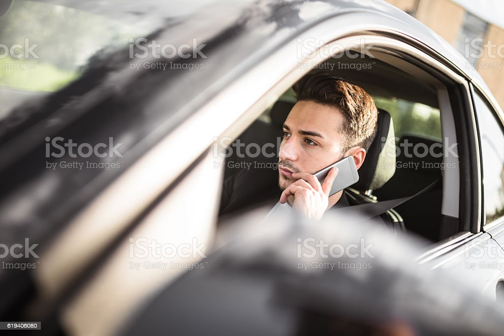 fashion man driving a black car stock photo