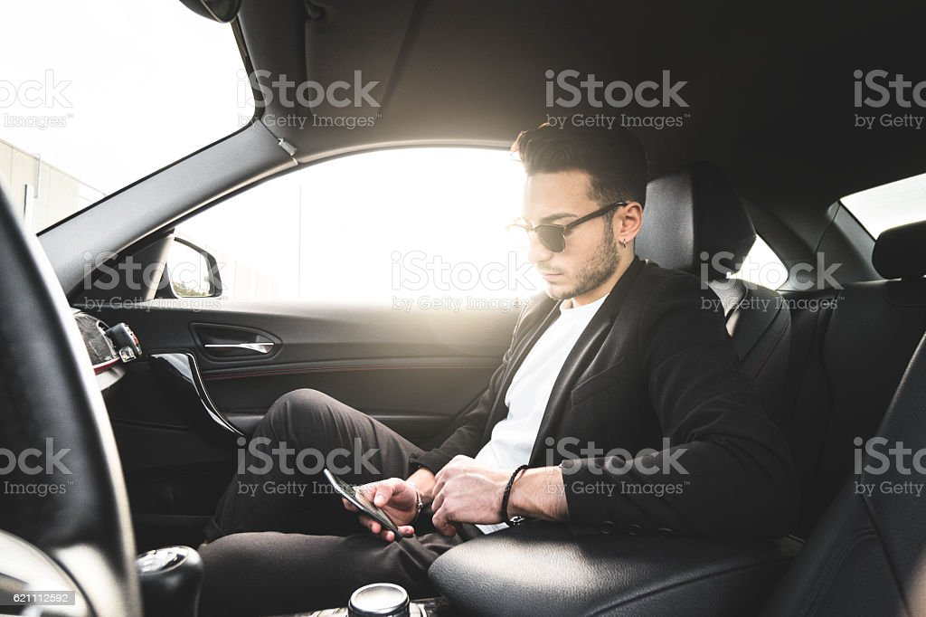 fashion man surfing with phone inside a car stock photo