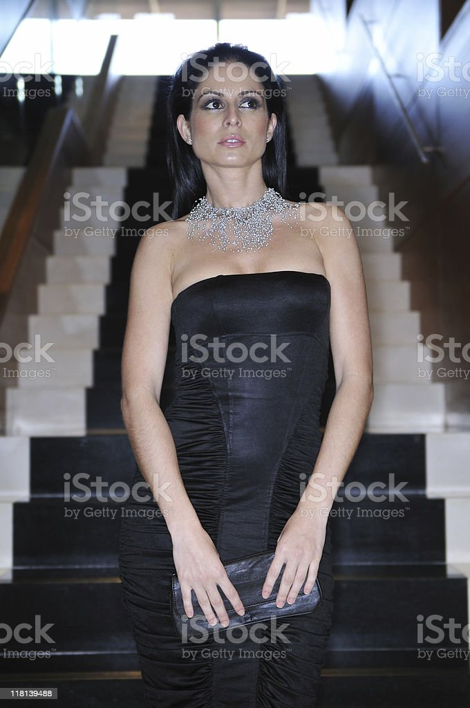 Fashion model brunette standing up in the stairs royalty-free stock photo