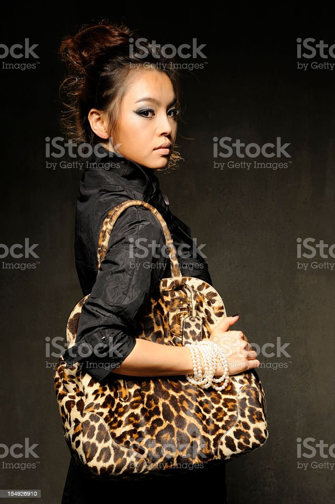 Fashion model carrying luxury leopard female bag royalty-free stock photo