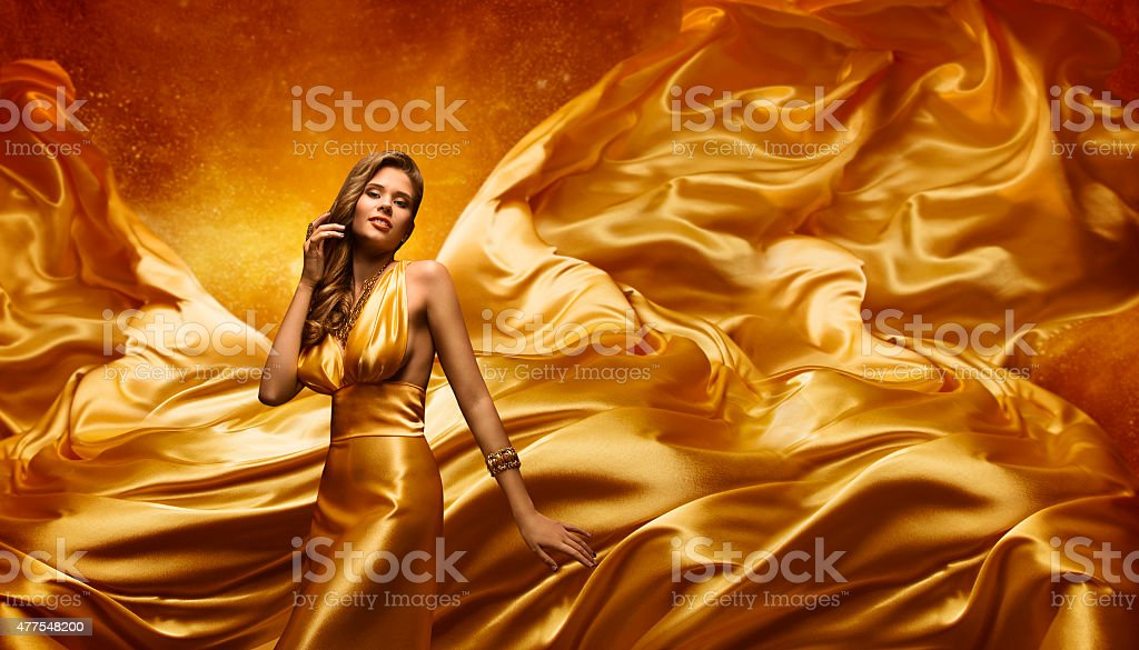 Fashion Model Gold Dress, Beauty Woman Posing Flying Waving Cloth stock photo