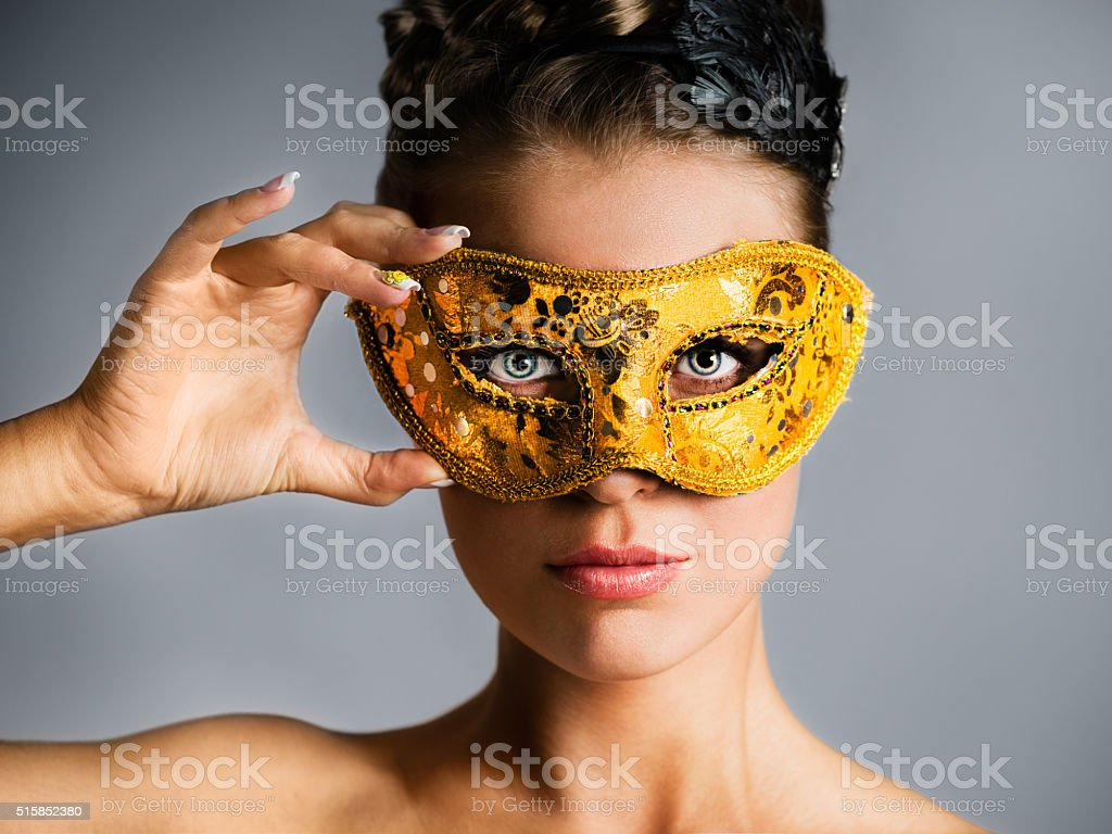 Fashion model hiding face behind golden mask stock photo