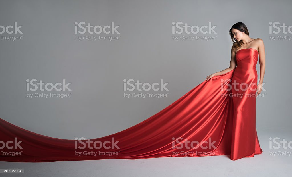 Fashion model in a red long dress stock photo