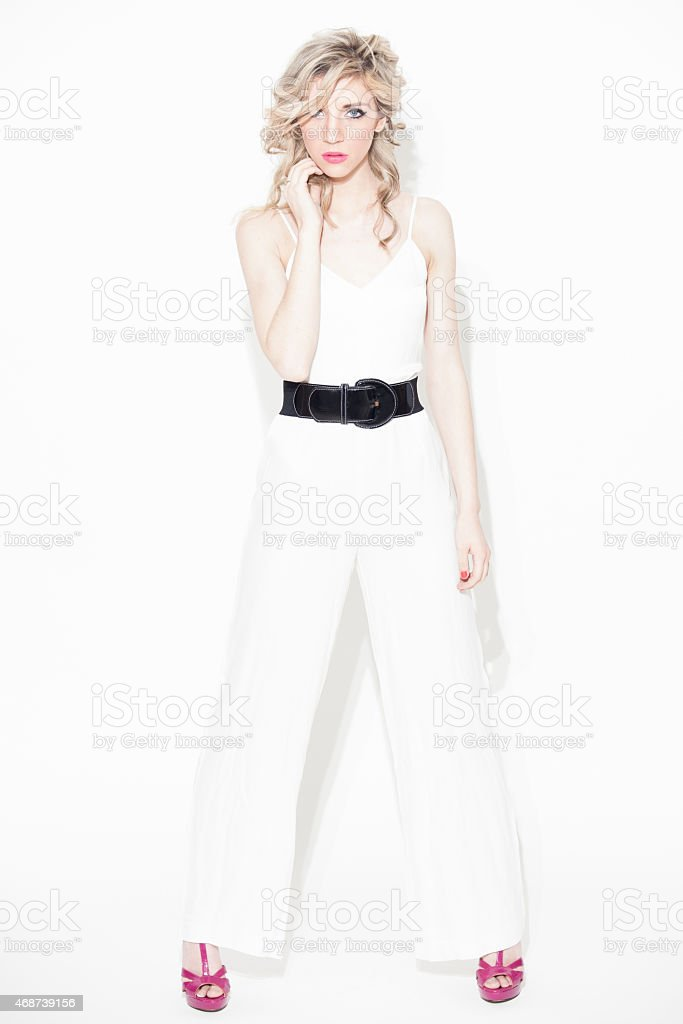 Fashion Model in White Jumpsuit on White Background stock photo