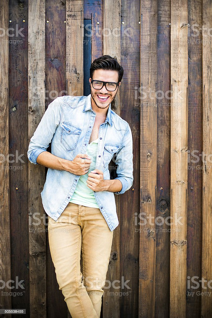 Fashion model leaning against a wooden wall stock photo